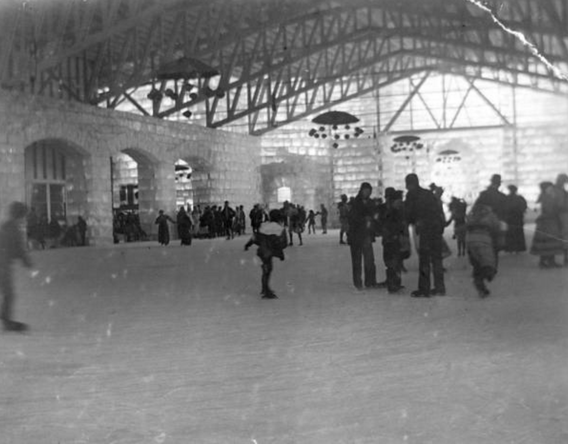 C.E. Joy designed the rink and Cobble & Kerr built the 80 x 190 foot structure. A skater is on the ice below the trussed roof. Ice arches are along the edge of the rink and umbrella-shaped chandeliers hang fourteen feet above the ice with mutli- colored electric lights. An exhibit can be seen through the arch in the background.