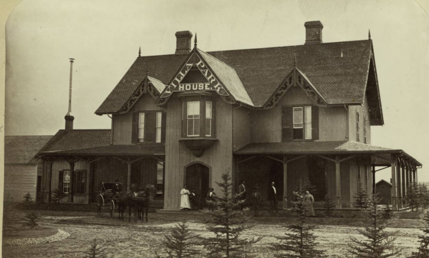 """Men and women, one man in a horse-drawn buggy, pose outdoors near the Villa Park House on The Boulevard (Federal Boulevard) in the Villa Park neighborhood of Denver, Colorado. The two-story hotel has a covered porch, decorative trim, and a sign that reads: """"Villa Park House"""".e title"""