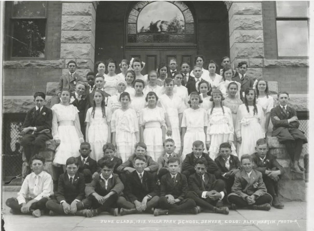 Boys and girls and their teachers pose on the steps of Villa Park School at 845 Hazel Court, Denver, Colorado. The boys sit or stand on the steps or on the ground and wear slacks, dress shirts, ties and jackets. The girls wear long dresses with lace, ruffles and bows. One girl wears a knitted hat.
