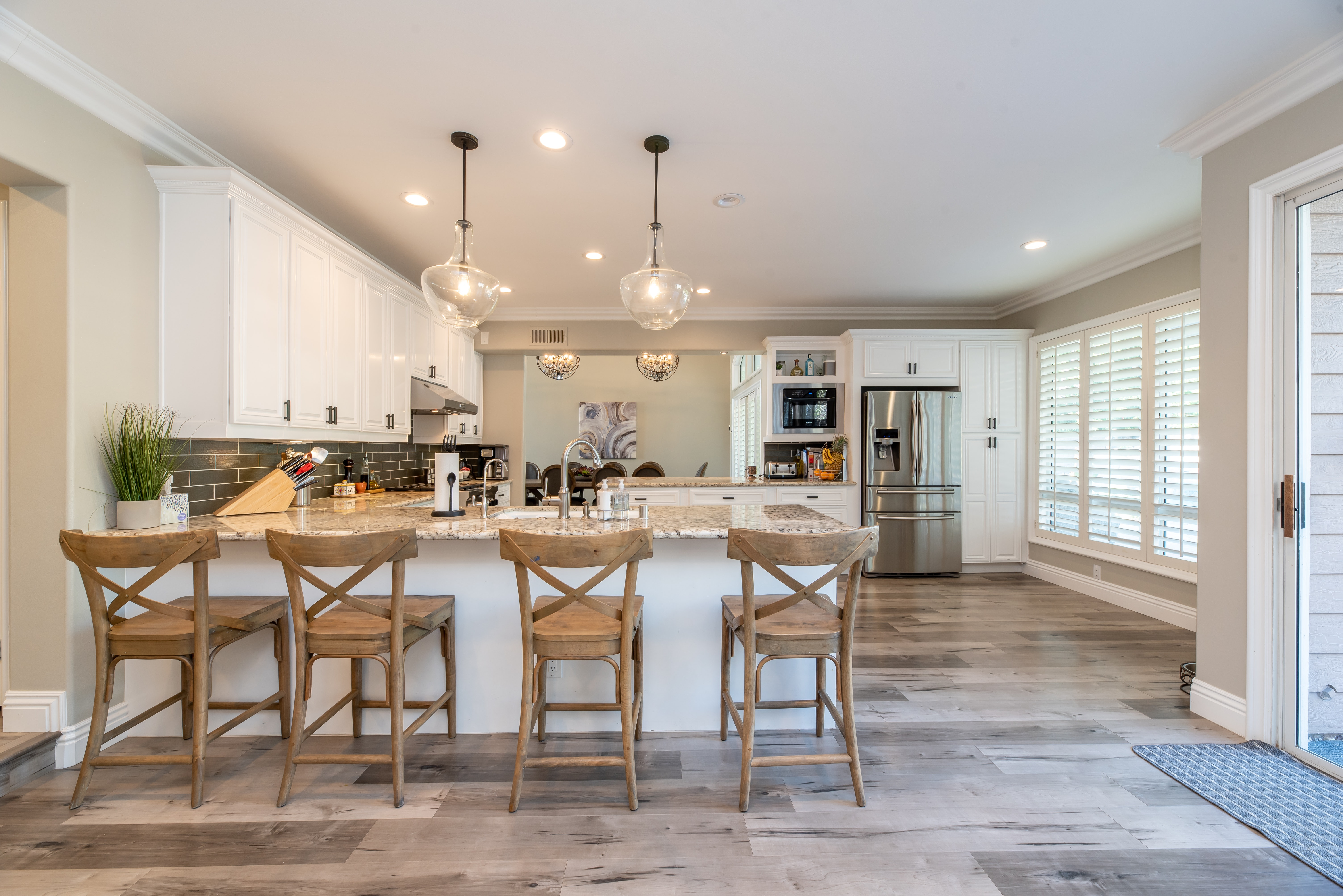 spacious kitchen with island and 4 stools and wooden floors