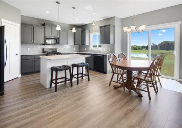 kitchen counter island with white cabinets and wood floors