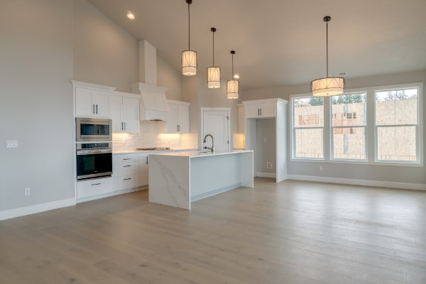 open concept kitchen with hardwood floors and stools