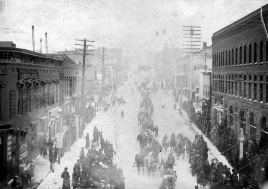 """Street scene of people dressed in winter coats and hats at a parade for the Ice Palace opening in Leadville (Lake County), Colorado. People are on horses or burros, in wagons, or beside commercial businesses. Signs read: """"Eye, Ear, Nose & Throat"""" """"Daly & Old Insurance"""" """"Assayer and Chemist"""" and """"Sam Erlich, Tailor."""""""