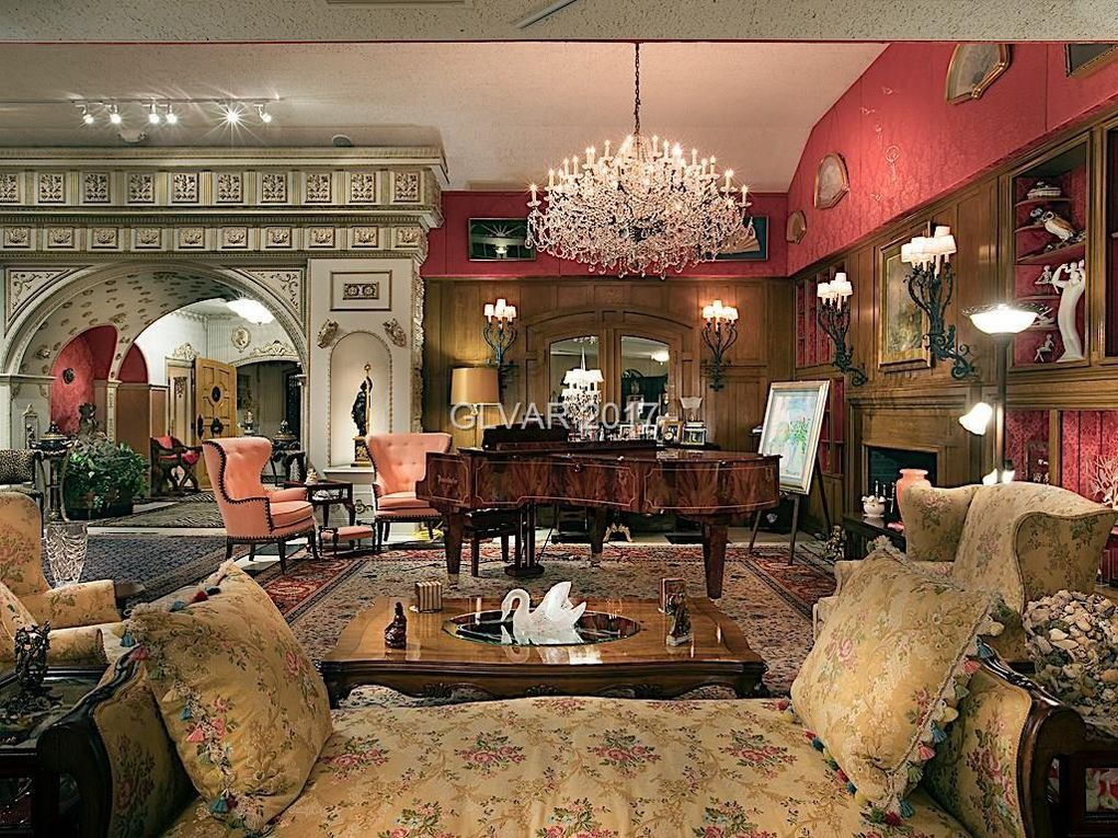 One of the many gathering rooms, including a gorgeous chandelier  that hangs over the stunning grand piano.
